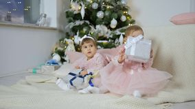 New year present, lovely little sisters sit on the floor with gift boxes against the background of christmas tree with stock footage