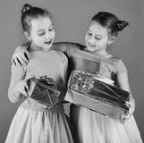 New Year presents concept. Sisters with wrapped gift boxes. Girls with curious faces hug holding presents on green background. New Year presents concept. Sisters Stock Image