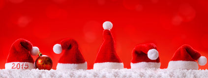 New Year 2015 red background with Christmas hats. Royalty Free Stock Images
