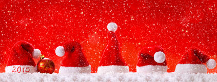 New Year 2015 red background with Christmas hats. Christmas Background and snowfall .New Year 2015 red background with Christmas hats Stock Photo