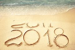 New Year 2018 replace 2017 on sea beach summer, New Year 2017 is coming concept. Closeup. stock photos