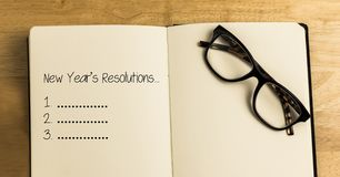 New year resolution goals in book with spectacles against wooden background. List of new year resolution goals in book with spectacles against wooden background royalty free illustration
