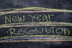 New Year Resolution handwritten text with colorful chalk on blackboard background royalty free stock image