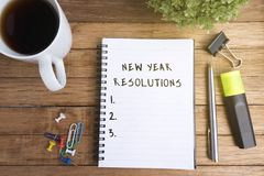 New Year Resolutions. On Notepad with Cup of Coffee and Office Supplies stock image