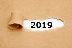 New Year 2019 Ripped Paper Concept. New year 2019 appearing behind ripped brown paper royalty free stock photo