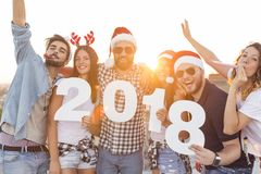 New Year Rooftop Party. Group of young friends celebrating New Year, dancing, singing and having fun at a building rooftop party royalty free stock photography
