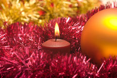 New Year's background. New Year's sphere a burning candle and a tinsel. Focus on a candle Stock Photography
