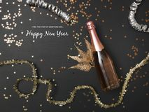 New Year´s background with a bottle of champagne and various New Year`s utensils on. New Year`s background with a bottle of champagne on black chalkboard royalty free stock photo