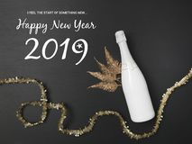 New Year´s background with a bottle of champagne and various New Year`s utensils on. New Year`s background with a bottle of champagne on black chalkboard stock image