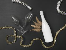 New Year´s background with a bottle of champagne and various New Year`s utensils on. New Year`s background with a bottle of champagne on black chalkboard royalty free stock image