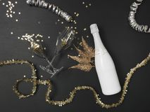 New Year´s background with a bottle of champagne and various New Year`s utensils on. New Year`s background with a bottle of champagne on black chalkboard royalty free stock photography