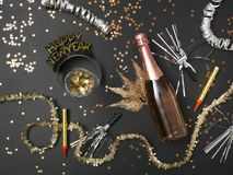 New Year´s background with a bottle of champagne and various New Year`s utensils on. New Year`s background with a bottle of champagne on black chalkboard stock photo