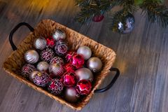 New year`s background. Christmas composition with basket, red and silver balls, a gray background. Christmas card. Background with copy space royalty free stock images