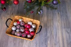 New year`s background. Christmas composition with basket, red and silver balls, a gray background. New Year`s card. Background with copy space stock photography