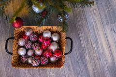 New year`s background. Christmas composition with basket, red and silver balls. Under the Christmas tree. New year`s background. Christmas composition with stock photography