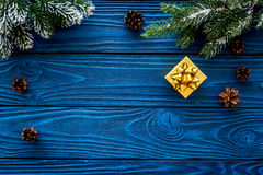 New year`s background. Christmas present, spruce branches, pine cone on blue wooden background top view copyspace Stock Photo
