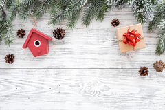 New year`s background. Christmas toys, present, spruce branches, pine cone on light wooden background top view copyspace Royalty Free Stock Images