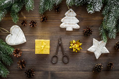 New year`s background. Christmas toys, present, spruce branches, pine cones on dark wooden background top view Royalty Free Stock Photography