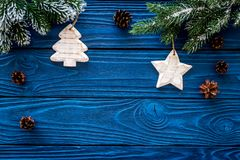 New year`s background. Christmas toys, spruce branches, pine cone on blue wooden background top view copyspace Royalty Free Stock Image