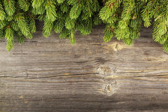 New Year`s background: fluffy green fir branches on a On atmospheric wooden background under the inscription with a free Stock Images