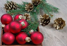 New Year background. New Year`s ball, branches of the Christmas tree and golden fir cones on a wooden table. royalty free stock image