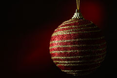 New Year's ball on a dark red background. Christmas ball with gold stripes on a dark red background Stock Photography