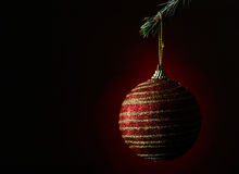 New Year's ball on a dark red background. Christmas ball hanging on a fir branch on a dark red background Stock Photos