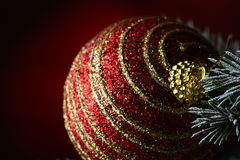 New Year's ball on a dark red background. Christmas ball hanging on a fir branch on a dark red background Stock Image