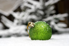 New Year's ball in a snow. On a background of a fur-tree Royalty Free Stock Photo