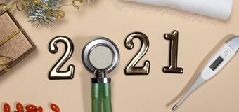 New Year`s banner on medical subjects: figures 2021, phonendoscope, thermometer with spruce branch on a beige background. New Yea