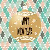 New Year`s bauble with the inscription Happy New Year on the background of a geometric pattern with rhombuses. Stock Photography
