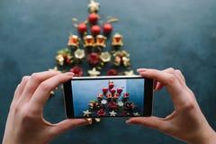 New Year`s blog mobile photo on dark background. Social media holidays. handmade christmas tree for winter holidays stock photo
