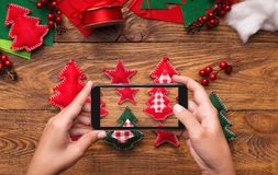 New Year`s blog mobile photo on wooden background. New Year`s blog. Woman making mobile photo of handmade felt toys on wooden background, social media holidays royalty free stock photo