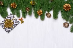 New year`s border on a white wooden background. Christmas decor. New year`s border on a white wooden background. Golden cones, a gift, a bell, a drum. Christmas Royalty Free Stock Photo