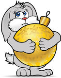 New Year's Bunny. Bunny hugs paws gold Christmas ball Royalty Free Stock Image