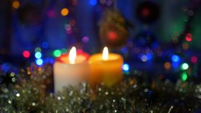 New Year`s candles close-up. Blurred background with colored lights. Moving the camera from the non-focus area to the. New Year`s candles, and Christmas stock footage