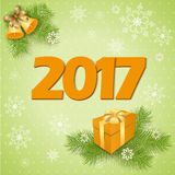New year`s card with gift. Vector design of 2017 new year`s image with gift box and bells on the green background with snowflakes.  EPS 10 Stock Photo