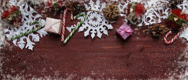 New Year`s Christmas concept. Snowflakes cut from paper, gifts, scissors on a wooden table. Banner Royalty Free Stock Photos