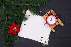 New Year`s or Christmas postcard. New Year`s postcard. An empty sheet of paper with a red clock, a wooden sledge, a flower of a punch and a Christmas tree, flat Stock Image