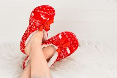 New Year`s, Christmas slippers for adults are dressed for the child. On white soft fur. Funny, funny, humorous, cozy,. New Year`s, Christmas slippers for adults Stock Photos
