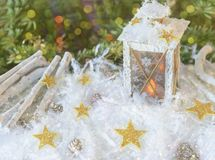 New Year`s, Christmas still life. Christmas handmade decorated lantern in snow with gold stars on green fir-tree background with Stock Images