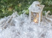 New Year`s, Christmas still life. Christmas handmade decorated lantern in snow with silver stars on green fir-tree background wit Stock Photos