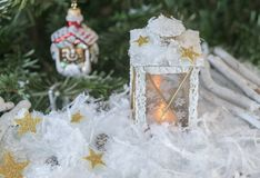 New Year`s, Christmas still life. Christmas handmade decorated lantern in snow with gold stars on green fir-tree background with Stock Image