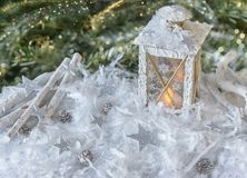 New Year`s, Christmas still life. Christmas handmade decorated lantern in snow with silver stars on fir-tree background with ligh Royalty Free Stock Photos