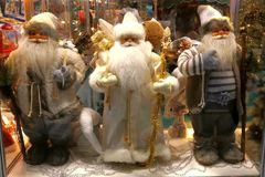 New Year`s and Christmas. Three Santa Claus in the shop window o Royalty Free Stock Photos