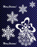 New Year`s or Christmas toy made of snowflakes with ribbon and bow. On a blue-and-black background Stock Photos