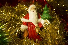New Year`s and Christmas toys - an ornament of a Santa Claus figure in a golden and red festive tinsel close-up royalty free stock photography