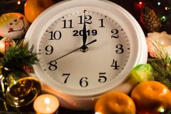 New Year's clock. Around tangerines, candles and Christmas tree. Happy New Year. Chimes beat 12 royalty free stock photo