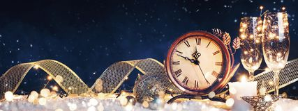 New Year`s clock with christmas decorations on snow stock image