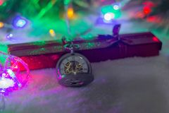 New Year`s clock. Christmas background. New Year`s clock and gift box. Christmas background Royalty Free Stock Image